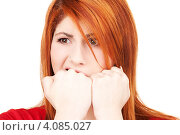 Купить «Несчастная рыжая женщина кусает кулаки на белом фоне», фото № 4085027, снято 10 октября 2009 г. (c) Syda Productions / Фотобанк Лори