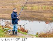 Купить «Счастливый рыбак стоит с удочкой на реке», эксклюзивное фото № 4091227, снято 5 ноября 2012 г. (c) Игорь Низов / Фотобанк Лори