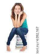 Купить «Студентка сидит на стопке книг, белый фон», фото № 4092167, снято 22 августа 2012 г. (c) Elnur / Фотобанк Лори