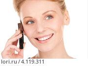 Купить «Жизнерадостная девушка с мобильным телефоном в руках на белом фоне», фото № 4119311, снято 12 декабря 2009 г. (c) Syda Productions / Фотобанк Лори