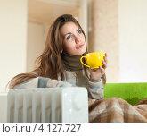 Купить «Красивая девушка с чашкой чая греется дома возле обогревателя», фото № 4127727, снято 20 октября 2012 г. (c) Яков Филимонов / Фотобанк Лори
