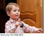 Счастливый маленький мальчик в наушниках слушает музыку на плеере. Стоковое фото, фотограф Игорь Низов / Фотобанк Лори