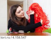 Купить «Девушка держит в руках яркий красный парик», фото № 4158547, снято 21 декабря 2012 г. (c) Яков Филимонов / Фотобанк Лори