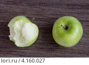 Целое и обкусанное яблоко на деревянном столе. Стоковое фото, фотограф Евстратенко Юлия Викторовна / Фотобанк Лори