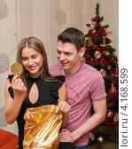 Купить «Счастливая пара. Парень с девушкой достают подарки из мешка возле новогодней ёлки», эксклюзивное фото № 4168599, снято 5 января 2013 г. (c) Игорь Низов / Фотобанк Лори