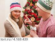 Купить «Счастливая пара. Весёлые парень и девушка с шоколадом возле новогодней ёлки», эксклюзивное фото № 4169439, снято 5 января 2013 г. (c) Игорь Низов / Фотобанк Лори