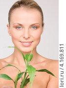 Купить «Молодая женщина с зеленым растением на белом фоне», фото № 4169811, снято 8 мая 2010 г. (c) Syda Productions / Фотобанк Лори