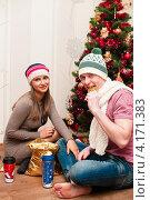 Счастливая пара.Молодые девушка и парень сидят на полу под новогодней ёлкой. Стоковое фото, фотограф Игорь Низов / Фотобанк Лори