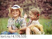 Счастливые мальчик и девочка сидят на траве. Стоковое фото, фотограф Дарья Петренко / Фотобанк Лори