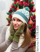 Грустная девушка в зимней шапке, варежках и шарфе на фоне новогодней ёлки. Стоковое фото, фотограф Игорь Низов / Фотобанк Лори