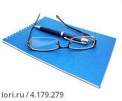 Купить «Очки и ручка лежат поверх синего блокнота», фото № 4179279, снято 9 января 2013 г. (c) Наталья Осипова / Фотобанк Лори