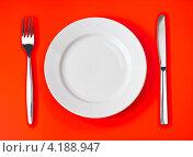 Купить «Белая пустая тарелка, нож и вилка на красном фоне», фото № 4188947, снято 14 декабря 2009 г. (c) Андрей Кузьмин / Фотобанк Лори