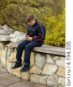 Купить «Подросток,  увлечённый мобильным телефоном», фото № 4194335, снято 20 октября 2012 г. (c) Самойлова Екатерина / Фотобанк Лори