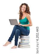 Купить «Студентка в джинсах и зелёной майке с ноутбуком на коленях сидит на стопке книг», фото № 4202443, снято 22 августа 2012 г. (c) Elnur / Фотобанк Лори