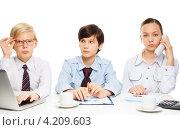 Купить «Дети сидят за столом с кофе и компьютером, претворяются деловыми людьми на белом фоне», фото № 4209603, снято 9 декабря 2012 г. (c) Сергей Новиков / Фотобанк Лори
