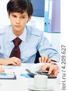 Купить «Бизнесмен. Серьезный подросток в рубашке и галстуке сидит за столом в офисе», фото № 4209627, снято 9 декабря 2012 г. (c) Сергей Новиков / Фотобанк Лори