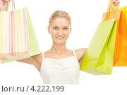 Купить «Счастливая молодая женщина держит в руках покупки в бумажных пакетах на белом фоне», фото № 4222199, снято 18 сентября 2010 г. (c) Syda Productions / Фотобанк Лори