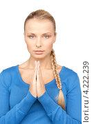 Купить «Молодая блондинка молится на белом фоне», фото № 4222239, снято 8 мая 2010 г. (c) Syda Productions / Фотобанк Лори
