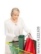 Купить «Счастливая молодая женщина держит в руках покупки в бумажных пакетах на белом фоне», фото № 4222639, снято 30 октября 2010 г. (c) Syda Productions / Фотобанк Лори