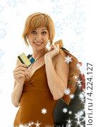 Купить «Счастливая девушка с покупками на фоне со снежинками», фото № 4224127, снято 19 августа 2006 г. (c) Syda Productions / Фотобанк Лори