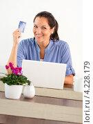 Купить «Радостная девушка с кредиткой за ноутбуком в гостиной», фото № 4228179, снято 23 сентября 2012 г. (c) CandyBox Images / Фотобанк Лори
