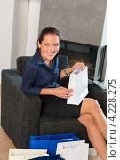 Купить «Счастливая девушка сидит на кресле с покупками», фото № 4228275, снято 23 сентября 2012 г. (c) CandyBox Images / Фотобанк Лори