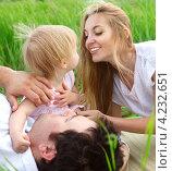 Счастливые родители с маленькой дочкой лежат в зеленой траве. Стоковое фото, фотограф Дарья Петренко / Фотобанк Лори