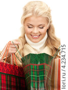 Купить «Привлекательная блондинка в зимней одежде с пакетами покупок в руках», фото № 4234715, снято 13 ноября 2010 г. (c) Syda Productions / Фотобанк Лори