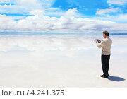 Мужчина стоит на отражающей поверхности озера и работает на планшете (2013 год). Стоковое фото, фотограф Dmitry Burlakov / Фотобанк Лори