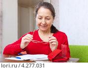 Купить «Женщина средних лет читает документы за столом», фото № 4277031, снято 9 декабря 2012 г. (c) Яков Филимонов / Фотобанк Лори