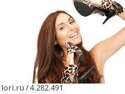 Купить «Счастливая брюнетка с длинными волосами прижимает к себе туфли на каблуке леопардовой расцветки», фото № 4282491, снято 6 ноября 2010 г. (c) Syda Productions / Фотобанк Лори