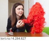 Купить «Шатенка держит в руке красный парик», фото № 4284827, снято 21 декабря 2012 г. (c) Яков Филимонов / Фотобанк Лори