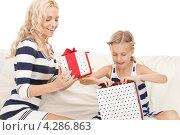 Купить «Счастливая мама с маленькой дочкой с подарками в коробках», фото № 4286863, снято 28 августа 2010 г. (c) Syda Productions / Фотобанк Лори