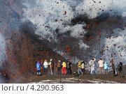 Туристы на фоне лавы, вырывающейся из кратера. Извержение вулкана Плоский Толбачик (Тулуач) на Камчатке (2013 год). Редакционное фото, фотограф А. А. Пирагис / Фотобанк Лори