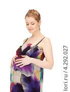 Купить «Молодая беременная женщина с длинными русыми волосами в сарафане на белом фоне», фото № 4292027, снято 12 марта 2011 г. (c) Syda Productions / Фотобанк Лори