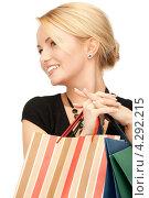 Купить «Довольная покупательница улыбается, стоя с пакетами в руках», фото № 4292215, снято 12 февраля 2011 г. (c) Syda Productions / Фотобанк Лори