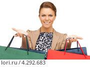 Купить «Довольная покупательница улыбается, стоя с пакетами в руках», фото № 4292683, снято 12 марта 2011 г. (c) Syda Productions / Фотобанк Лори