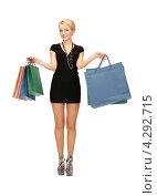 Купить «Довольная покупательница улыбается, стоя с пакетами в руках», фото № 4292715, снято 12 февраля 2011 г. (c) Syda Productions / Фотобанк Лори