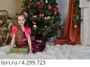 Красивая девочка 9 лет сидит на белом пушистом ковре на фоне новогодней елки с подарком. Стоковое фото, фотограф Вера Зонова / Фотобанк Лори