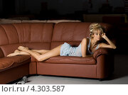 Девушка в одиночестве лежит на кожаном диване. Стоковое фото, фотограф Syda Productions / Фотобанк Лори