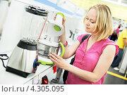 Купить «Молодая женщина выбирает бытовую технику в супермаркете», фото № 4305095, снято 23 июля 2012 г. (c) Дмитрий Калиновский / Фотобанк Лори