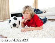 Купить «Ребенок болеет парад телевизором за футбольную команду, лежа рядом с футбольным мячом», фото № 4322423, снято 12 ноября 2019 г. (c) Wavebreak Media / Фотобанк Лори