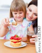 Купить «Девочка с мамой наливают на вафли мед», фото № 4325567, снято 18 октября 2009 г. (c) Wavebreak Media / Фотобанк Лори