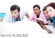 Купить «Озабоченные врачи и медицинская сестра у кровати темнокожего пациента смотрят в одну сторону», фото № 4332023, снято 24 февраля 2019 г. (c) Wavebreak Media / Фотобанк Лори