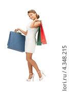 Купить «Красивая девушка на белом фоне держит в руках пакеты с покупками», фото № 4348215, снято 28 августа 2011 г. (c) Syda Productions / Фотобанк Лори