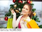 Купить «Счастливая девушка укладывает подарки под рождественскую елку», фото № 4349503, снято 21 января 2020 г. (c) Syda Productions / Фотобанк Лори