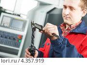 Купить «Работник измеряет деталь инструмента с помощью штангенциркуля», фото № 4357919, снято 15 февраля 2012 г. (c) Дмитрий Калиновский / Фотобанк Лори