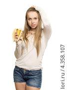 Купить «Длинноволосая молодая девушка держит в руке надкушенный банан», фото № 4358107, снято 28 февраля 2012 г. (c) Сергей Сухоруков / Фотобанк Лори