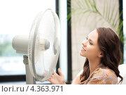 Купить «Счастливая молодая женщина сидит перед вентилятором», фото № 4363971, снято 16 июля 2011 г. (c) Syda Productions / Фотобанк Лори