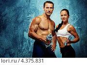 Купить «Спортивные мускулистые мужчина и женщина с гантелями», фото № 4375831, снято 31 июля 2011 г. (c) Andrejs Pidjass / Фотобанк Лори